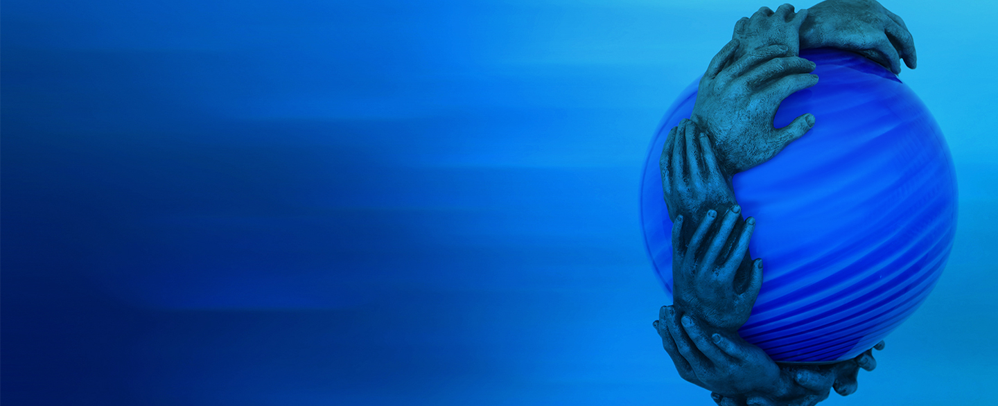 Sculpture of several hands surrounding a blue globe.