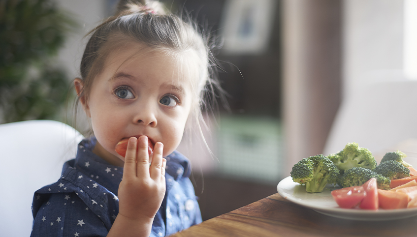 Little girl eating her vegetables.