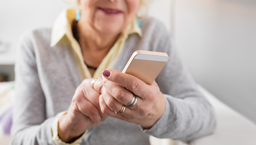 Older woman using cell phone.