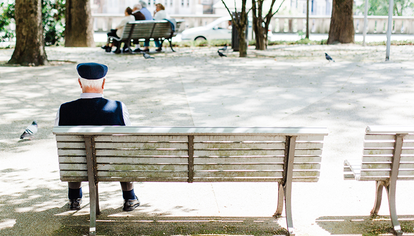 Man sitting alone on a park bench.