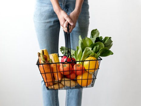 Woman holding a grocery basket full of vegetables.