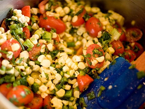 Corn and tomato salad being mixed in bowl.