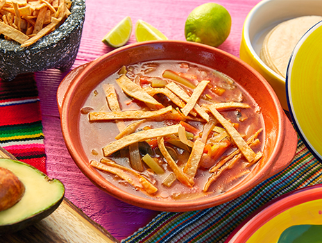 Bowl of enchilada soup with tortilla strips on top.