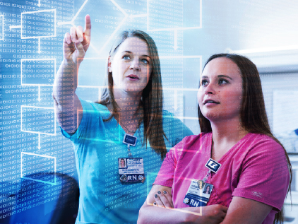 Two nurses looking at data on screen.
