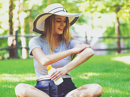 Girl in sun hat applying sunscreen.