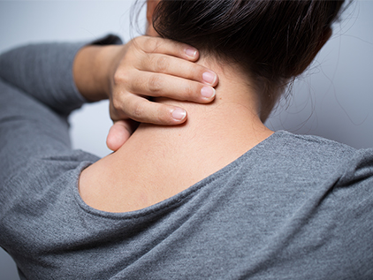 Woman holding her neck in discomfort.