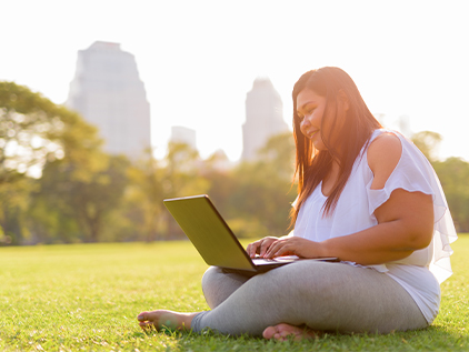 Woman sitting in park on computer