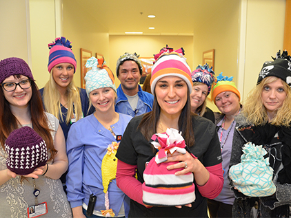 Group of nurses holding hats for Caps for Cancer.